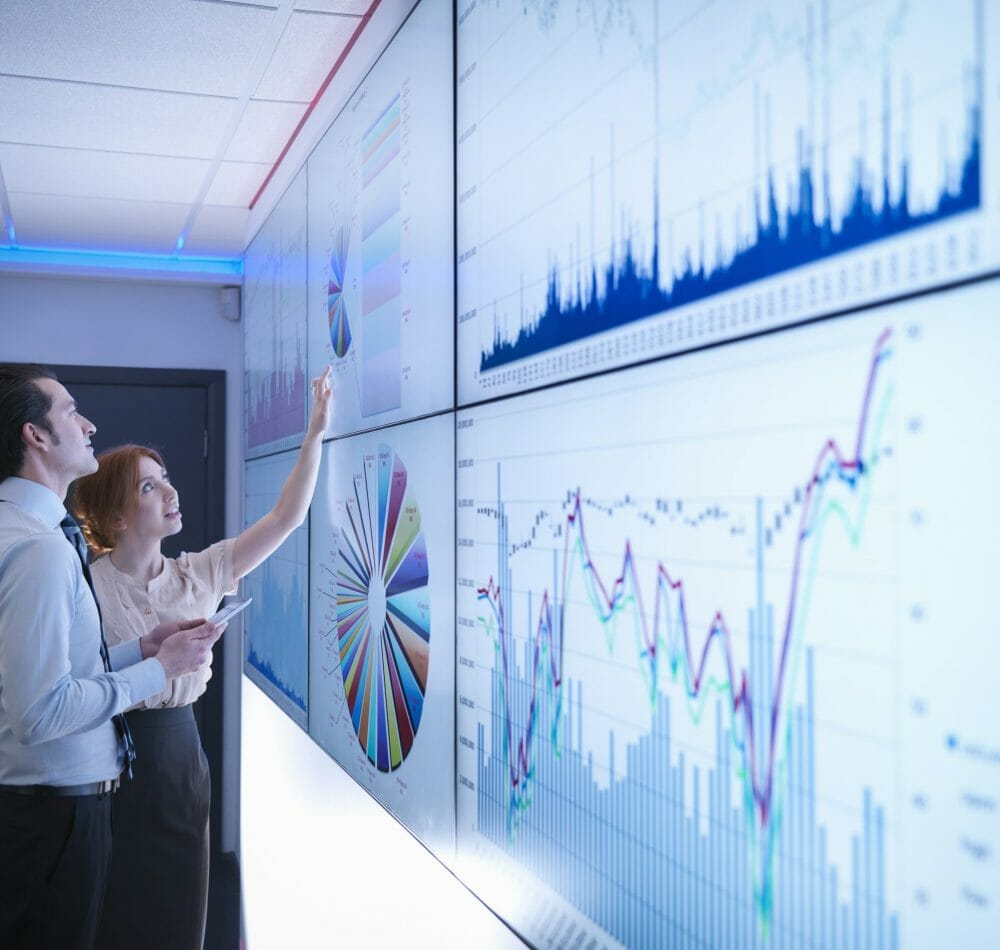 Business colleagues studying graphs on screen in meeting room